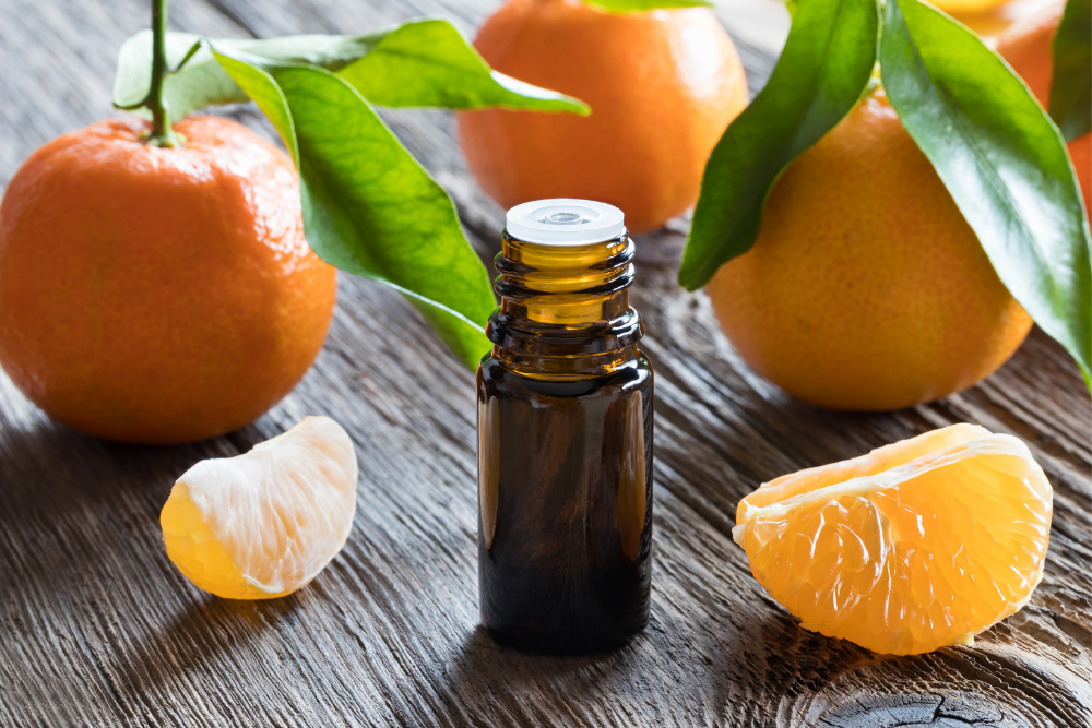 Tangerines with essential oil bottle